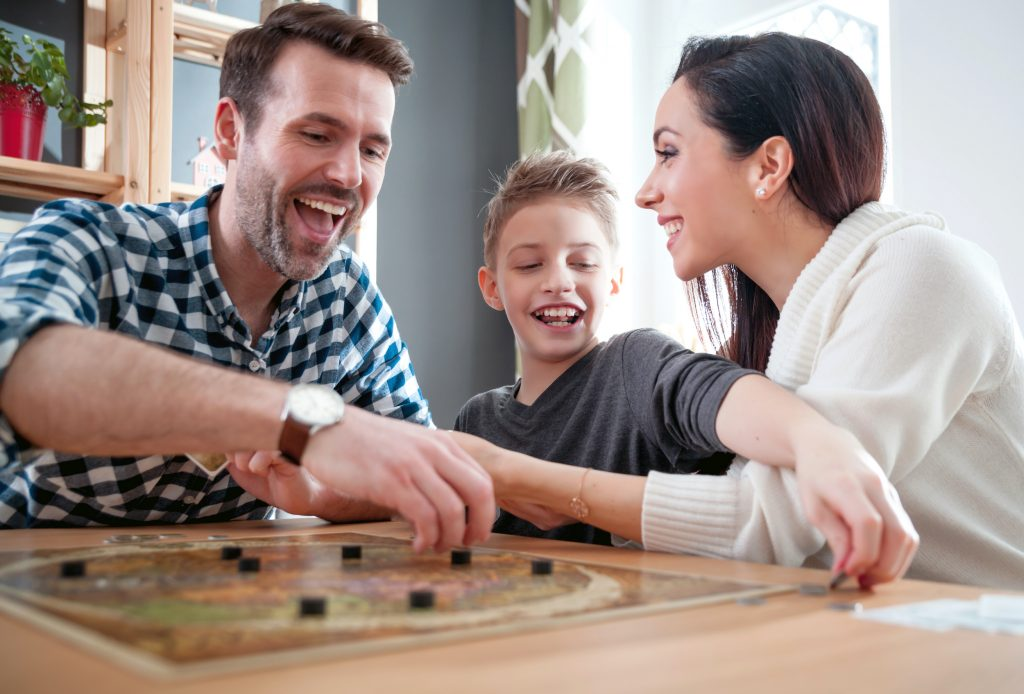 Husband and wife with tween son in between them laughing and playing a board game.