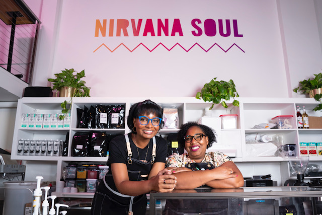 Two smiling women standing in front of colorful sign that says Nirvana Soul